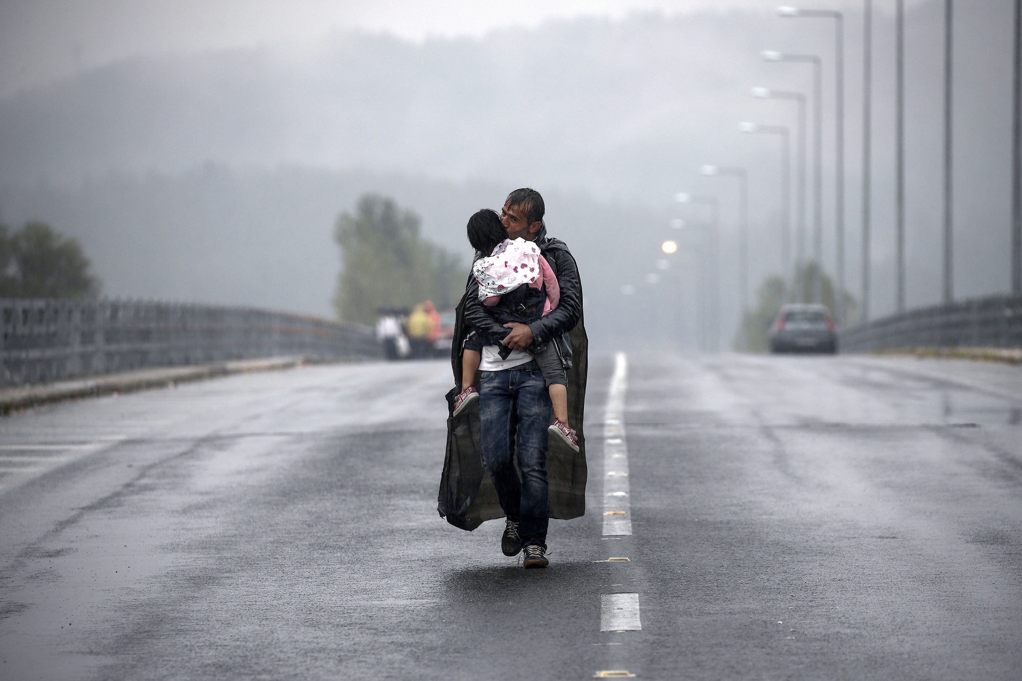 A Syrian refugee kisses his daughter as he walked for hours through a rainstorm to reach Greece's border with FYRO-Macedonia, near the Greek village of Idomeni, September 10, 2015. Thousands of refugees and migrants, including many families with young children, have been left soaked after spending the night sleeping in the open in torrential rain on the Greek- FYRO Macedonian border. About 7,000 people waited in the mud at an open field near the northern Greek village of Idomeni to cross the border, with more arriving in trains, buses and taxis, as FYRO Macedonian police has imposed rationing in the flow of refugees.